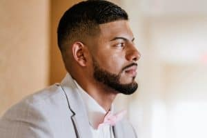 groom looking away from camera. Healthy skin, beard and hair groomed and styled sharply.