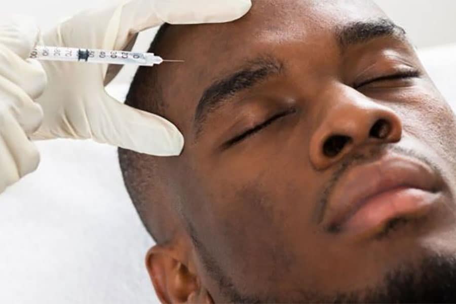 man receiving botox injection on forehead