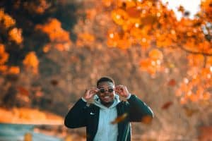 man smiling outside with autumn leaves